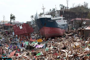 Typhoon hits Tacloban: survivors walk past a ship on top of damaged homes after it was washed ashore