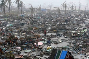 Typhoon hits Tacloban: people stand among debris and ruins of houses destroyed after typhoon