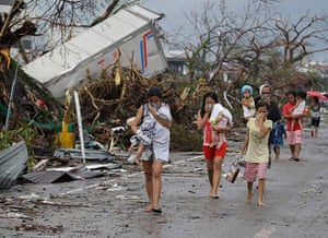 Typhoon hits Tacloban: residents cover their noses as they walk near dead bodies