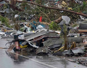 Typhoon hits Tacloban: a woman shelters in the remains of her damaged house