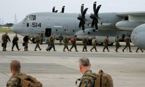 US Marine Corps soldiers forces board an aid aircraft leaving a US base on Okinawa in southern Japan for the Philippines