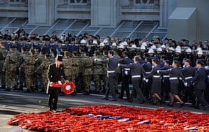 Remembrance Sunday: A steward arranges poppy wreaths as servicemen and women of the armed force