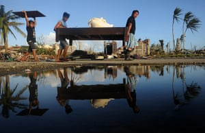 Tacloban survivors: Residents carry furniture from a hotel in Palo