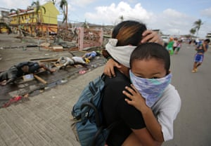 Tacloban survivors: A mother holding a baby covers her nose as she walks past dead bodies at th