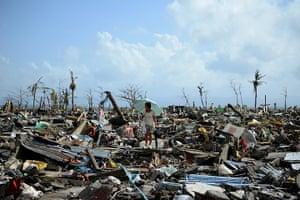 Tacloban survivors: A survivor walks among the debris of houses in Tacloban