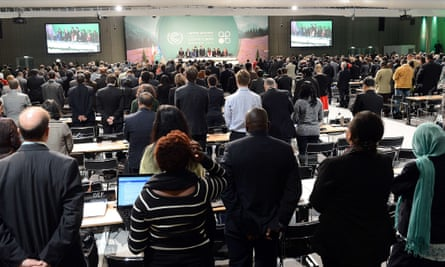 Participants of the UN climate talks conference in Warsaw pay standing tribute to victims of the deadly Philippines typhoon Haiyan