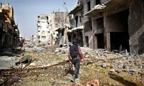 A fighter from an Islamist Syrian rebel group walks among damaged houses in Aleppo