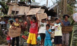 Children hold signs asking for help and food along the highway, after Typhoon Haiyan hit Tabogon town in Cebu Province, central Philippines November 11, 2013.