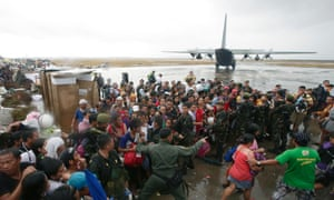 Typhoon survivors rush to get a chance to board a C-130 military transport plane in Tacloban on Tuesday.