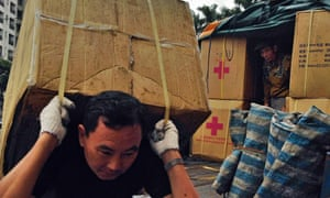 Volunteer workers of the Red Cross Society of Taiwan in Taipei carrying relief goods destined for the Philippines.