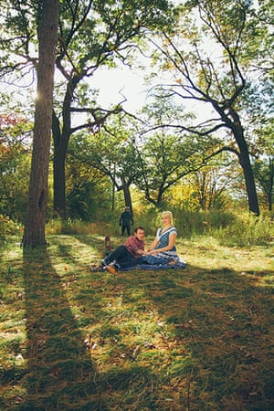 Big Picture - Friday 13th: couple sitting on grass with masked man in background