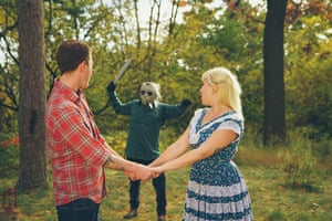 Big Picture - Friday 13th: couple holding hands in forest with masked man in background