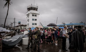 Thyphoon victims wait to be evacuated at the airport in Tacloban, on the eastern island of Leyte on 12 November 2013 after Super Typhoon Haiyan swept over the Philippines. T