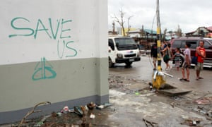 Residents walk along a downtown street past graffiti on a wall displaying the message 'save us' in typhoon hit Tacloban, Leyte, Philippines.