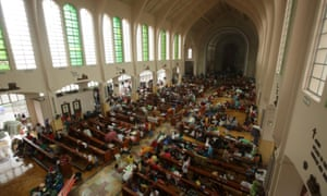Filipinos take shellter inside a church turned into a temporary evacuation centre in Tacloban