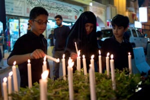 Youths light candles at a candlelight vigil to show their solidarity with victims of Super Typhoon Haiyan, in Manama November 12, 2013.