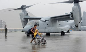 An elderly man on a wheelchair who survived the wrath of Super Typhoon Haiyan in the central coastal city of Tacloban disembarks from a US KC-130 military cargo plane that flew him and other people out of the city to Manila.