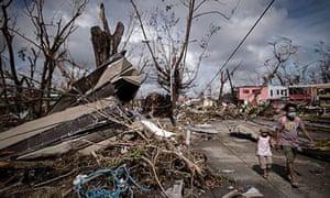 Typhoon victims walk past a piece of met