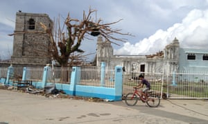A boy rides past the devastated church in the centre of Guiuan, where typhoon Haiyan first made landfall.