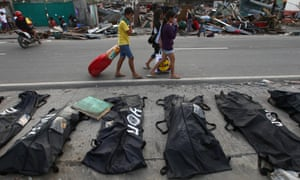 People cover their noses from the stench of dead bodies in an area affected by Typhoon Haiyan in Tacloban.