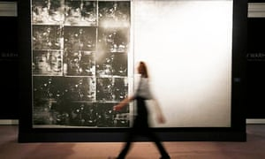A Sotheby's employee walks in front of Andy Warhol's artwork Silver Car Crash (Double Disaster)