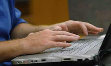 Man's hands typing on laptop.