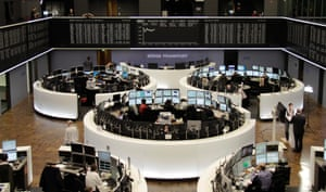 Traders are pictured at their desks in front of the DAX board at the Frankfurt stock exchange November 14, 2013.