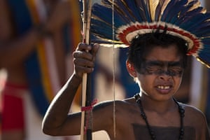 Indigenous Games: A Manoki Indian boy reacts in pain after having his nose pierced