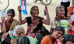 Tamil women hold portraits of missing relatives at a protest in Jaffna during David Cameron's visit