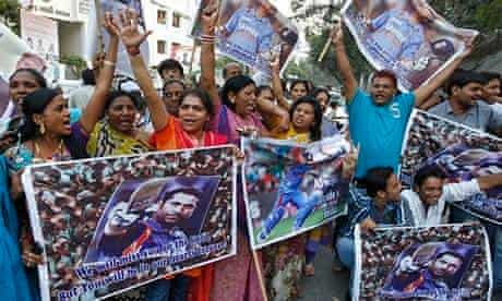 Fans hold posters of Indian cricketer Sachin Tendulkar in Ahmedabad