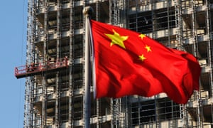 A Chinese national flag flutters at a construction site for a new residential complex in Beijing, in this November 4, 2013 file picture.