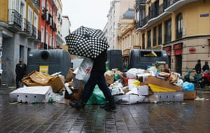 A pedestrian walks next to garbage strewn on the pavement during a strike by street cleaners in Madrid November 17, 2013.