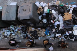 Women walk past a pile of rubbish surrounding trash containers during the eleventh day of a garbage collectors strike, Madrid, Spain, Friday, Nov. 15, 2013.