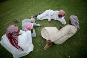 From the agencies camels: Camel handlers relax on the manicured grass between races