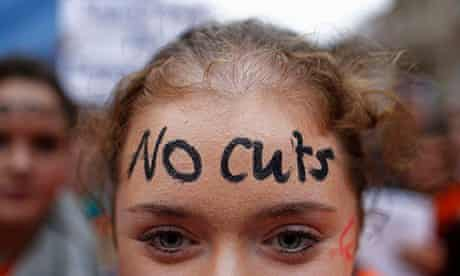 Irish teacher protesting againstcuts, with a 'no cuts' sign on her forhead