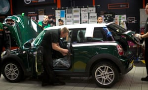 Factory workers produce Mini cars at the BMW's plant at Cowley in Oxford, central England, on November 18, 2013.