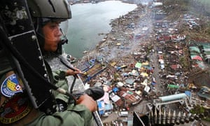 A Philippine Air Force crewman looks out over the typhoon Haiyan-ravaged city of Tacloban