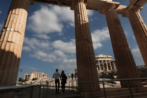 Visitors walk through Propylaia, the ancient Acropolis gateway, as the Parthenon temple (R) is seen in the background in Athens November 19, 2013