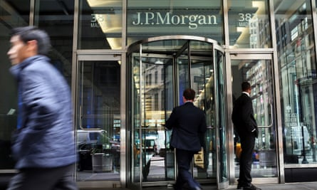 People pass a sign for JP Morgan's Manhattan headquarters.