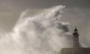 Waves crash against a lighthouse during the St Jude's Day storm