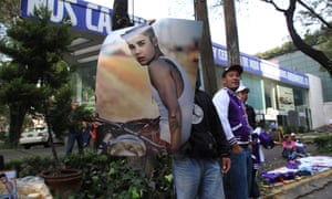 A street vendor hawks Justin Bieber merchandise outside the Mexico City hotel where the teen idol is staying.