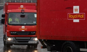 Royal Mail vans drive out of a sorting office in London.