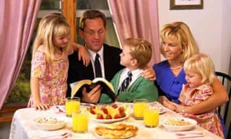 Family with three children having breakfast