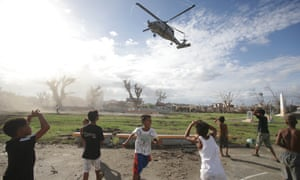 Help arrives. Typhoon survivors watch as a US helicopter lands to deliver relief goods in Tanauan, Leyte province, central Philippines today.