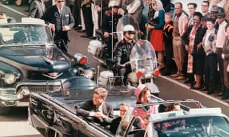 JFK and Jackie Kennedy smile at the crowds lining their motorcade route in Dallas, Texas, on November 22, 1963.
