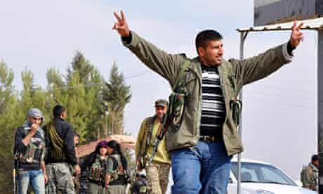 A member of the Kurdish People's Protection Units (YPG) flashes a victory sign in Ras al-Ain