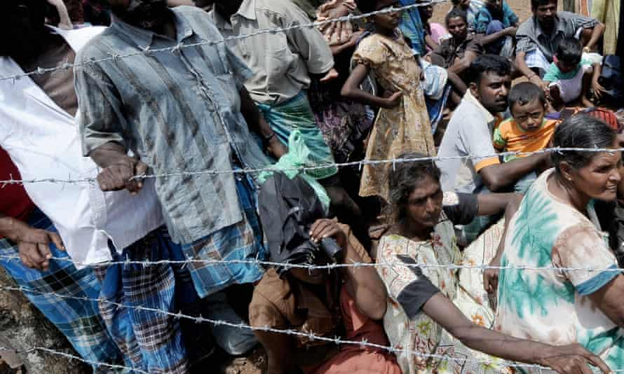 Internally displaced Sri Lankan people wait behind barbed wire during a visit by United Nations Secretary-General Ban Ki-moon in 2009.
