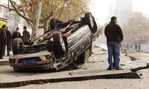 An overturned car and buckled pavement after the Qingdao oil pipeline explosion