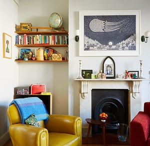 homes bold colourful lounge with yellow armchair and cast iron fireplace
