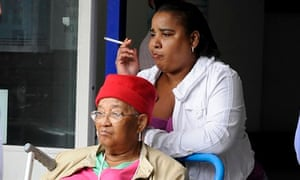 A visitor smokes in  entrance of a hospital